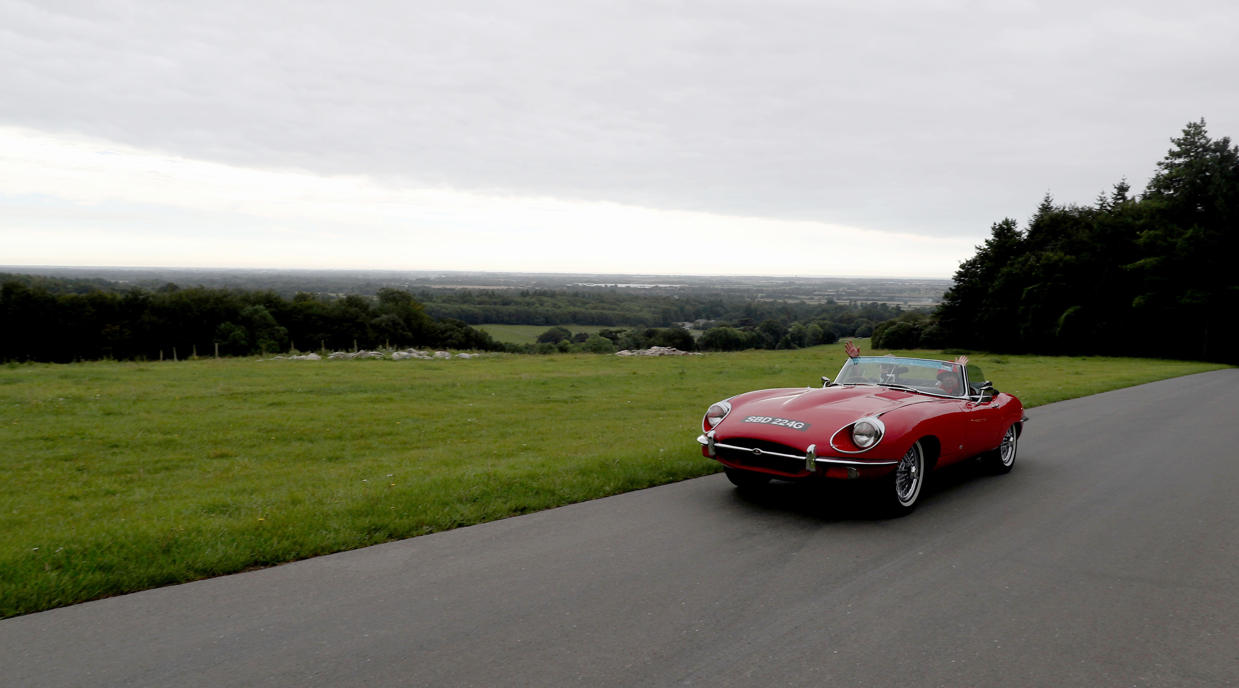 Red classic jaguar on a countryside drive