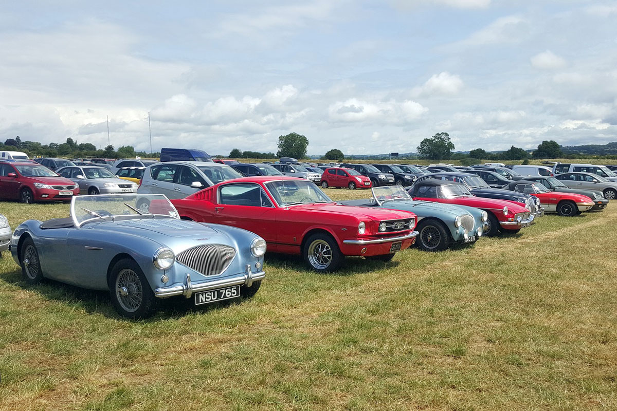 1955 blue Austin Healey next to Ford Mustang and other vehicles