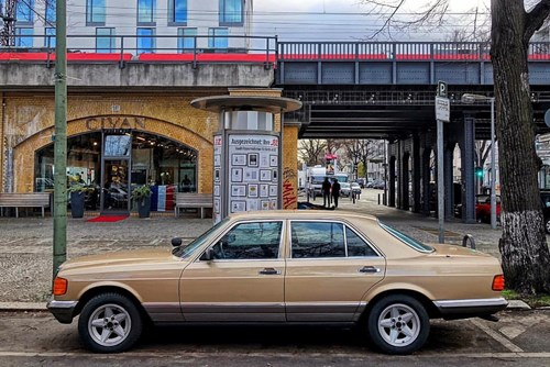 Gold Mercedes-Benz W126 parked on a road