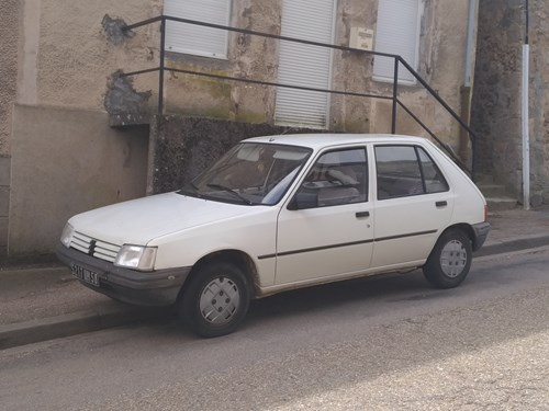 White Peugeot 205 parked on the side of a road